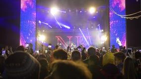 Os fãs da multidão com o smartphone nas mãos tomam a música ao vivo do prazer no evento da rocha em luzes brilhantes da cena na n video estoque