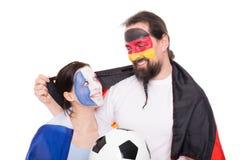 Os fãs de futebol de França e de Alemanha estão abraçando, futebóis e Fl Fotografia de Stock Royalty Free