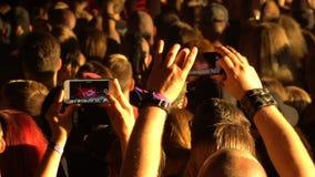Os fãs disparam em um concerto de rocha video em telefones celulares video estoque