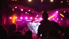 Os fãs que saltam e que acenam a cabeça no festival da música ao vivo em brilhante iluminado por projetores video estoque