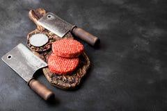 Os fazendeiros caseiros triturados crus frescos grelham hamburgueres da carne na placa de desbastamento do vintage com especiaria imagens de stock