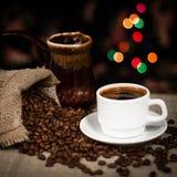 Os feijões da xícara de café e de café dispersaram na tabela, ainda vida com efeito do bokeh Imagem de Stock