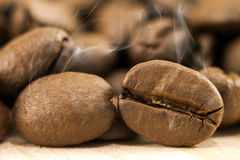 Os feijões de café de Brown com fumo branco vaporizam no wo textured amarelo Imagem de Stock