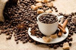 Os feijões de café derramaram no copo e os pires e um saco do café Fotografia de Stock