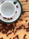 Os feijões de café dispersaram na tabela de madeira ao lado de um copo vazio em uns pires com uma borda verde na esquerda Imagens de Stock