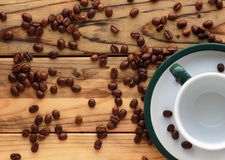 Os feijões de café dispersaram na tabela de madeira ao lado de um copo vazio em uns pires com uma borda verde no canto inferior d Imagem de Stock Royalty Free