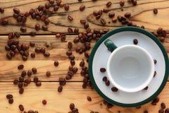 Os feijões de café dispersaram na tabela de madeira ao lado de um copo vazio em uns pires com uma borda verde no canto inferior d Imagem de Stock