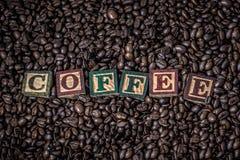 Os feijões de café em grãos de café de uma caixa de madeira com o de madeira no texto são café Imagens de Stock Royalty Free