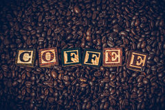 Os feijões de café em grãos de café de uma caixa de madeira com o de madeira no texto são café Foto de Stock