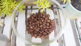 Os feijões de café empilham no montão de vidro na tabela de madeira, vista superior imagem de stock royalty free