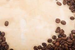 Os feijões de café estão em um semicírculo no papel velho Foto de Stock