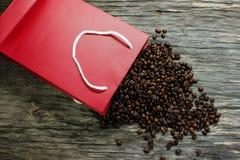 Os feijões de café foram dispersados da embalagem vermelha em uma tabela de madeira Fotografia de Stock