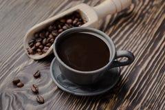 Os feijões de café forte do preto, café, enegrecem feijões e o copo roasted de café da goma-arábica completamente do café Imagens de Stock
