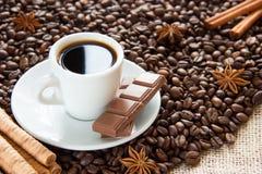 Os feijões de café fritados com um copo em uns pires com um café bebem com chocolate da canela e do anis e de leite foto de stock