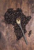 Os feijões de café Roasted arranjaram na forma de África na madeira velha Fotografia de Stock Royalty Free