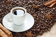 Os feijões de café Roasted com um copo em uns pires com um café bebem com canela e anis imagens de stock
