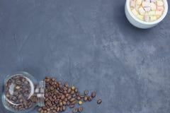 Os feijões de café Roasted, derramaram de um frasco de vidro com uma xícara de café e um marshmallow brancos colocação angular do imagens de stock