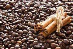 Os feijões de café Roasted são dispersados e um grupo de varas de canela foto de stock