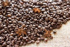 Os feijões de café Roasted são dispersados no pano de saco com anis fotografia de stock