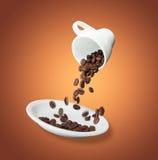 Os feijões de café são derramados de um copo em uns pires fotografia de stock