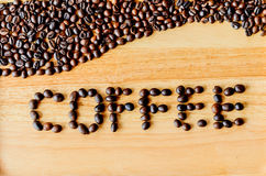 Os feijões de café são literalmente ` do café do ` em um assoalho de madeira imagem de stock