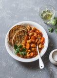 Os feijões-de-lima assados picantes no molho de tomate e no ciabatta brindam em um fundo cinzento Proteína deliciosa do vegetal d fotografia de stock royalty free