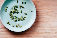 Os feijões de mung secos verdes dispersaram em uns pires, vista superior foto de stock