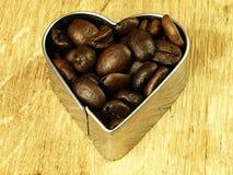 Os feijões do coração e de café fecham-se acima na tabela de carvalho de madeira Foto de Stock