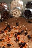 Os feijões e a grão misturam nos frascos de vidro em uma tabela de madeira Imagem de Stock Royalty Free