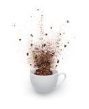 Os feijões e o pó de café derramaram para fora do copo Fotografia de Stock Royalty Free
