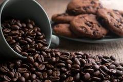 Os feij?es de caf? desintegraram-se com um copo, no fundo uma placa das cookies fotos de stock royalty free