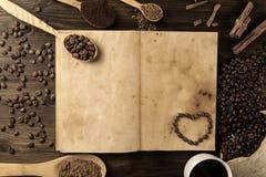 Os feijões de café no vintage velho abrem o livro Menu, receita, zombaria acima Fundo de madeira Imagens de Stock Royalty Free