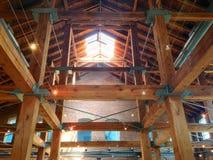 Os feixes de madeira esboçam o interior de um homem feito estrutura com tijolo e metal imagens de stock