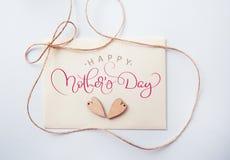 Os feriados cardam com dia de mães feliz de madeira do coração e do texto Tração da mão da rotulação da caligrafia imagem de stock