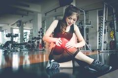 Os ferimentos asiáticos da mulher durante o exercício no joelho no gym da aptidão Medi fotos de stock royalty free