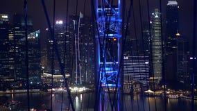 Os ferris grandes rodam dentro a skyline moderna da cidade, vista em Singapura da roda na noite 3840x2160 vídeos de arquivo