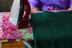 Os ferros vermelhos, ferros passando, donas de casa fazem o smoother das telas Foto de Stock