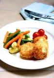Os fishcakes Salmon seriram com vegetais e tomates de cereja. fotos de stock royalty free