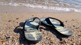 Os flip-flops estão no litoral, flip-flops pretos na praia vídeos de arquivo