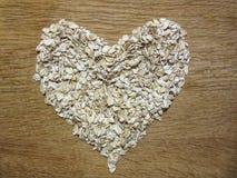 Os flocos da aveia empilham em uma forma do coração em um fundo de madeira imagem de stock royalty free