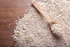 Os flocos da aveia na colher de madeira na aveia lascam-se fundo Comer e estilo de vida saudáveis Imagem de Stock