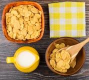 Os flocos de milho em umas bacias, em um guardanapo e em um jarro ordenham na tabela Fotografia de Stock Royalty Free