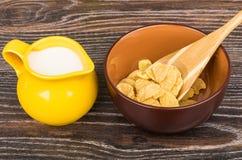 Os flocos de milho na bacia e no jarro marrons ordenham na tabela Imagens de Stock Royalty Free