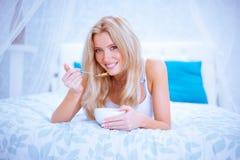 Os flocos de milho saudáveis tomam o café da manhã na mulher da cama que come e feliz foto de stock
