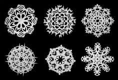Os flocos de neve cortaram do papel em um fundo preto Fotografia de Stock