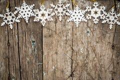 Os flocos de neve limitam na madeira Imagens de Stock