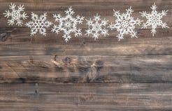 Os flocos de neve limitam sobre o fundo de madeira Decoração do Natal Fotos de Stock Royalty Free