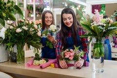 Os floristas fêmeas estão criando ramalhetes imagem de stock royalty free