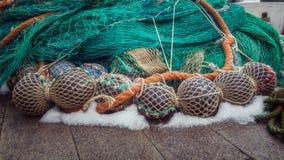 Os flutuadores e uma rede de pesca verde são empilhados acima foto de stock