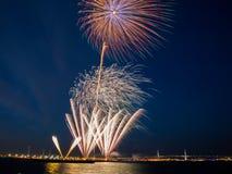 Os fogos-de-artifício brilhantes estouraram no céu azul com luzes e água do mar distantes da cidade fotos de stock royalty free